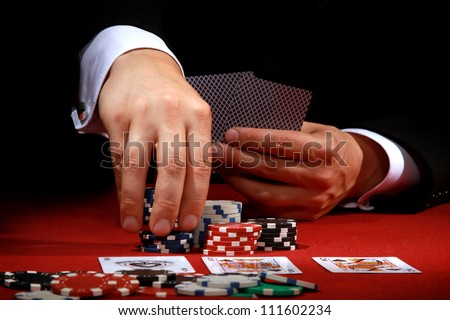 Man playing poker on red background - stock photo
