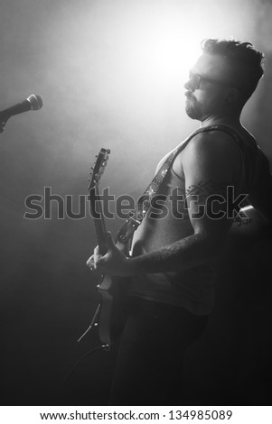 Man playing rock concert with attitude. Sings and play guitar.