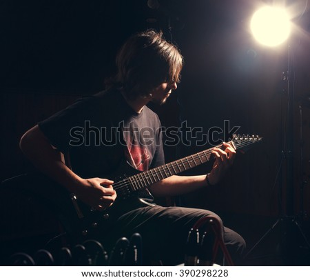 Man playing rock musik on bass guitar - stock photo