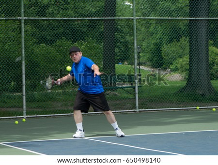 Man playing tennis in Central Park tennis court