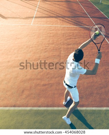 Man playing tennis on the tennis court - stock photo