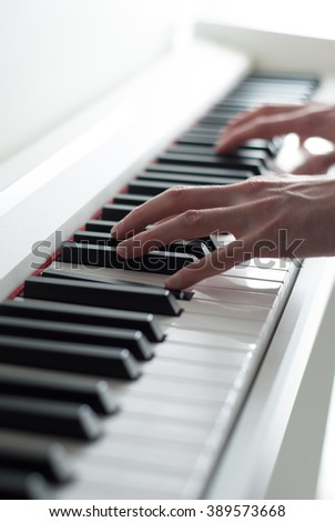 Man playing the piano. Piano keys. Piano playing. Black and white keys. Electronic piano. Musical instrument.