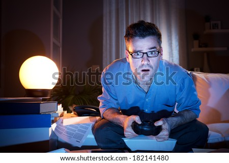Man playing videogames late at night in a messy living room, sitting on sofa. - stock photo