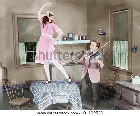 Man playing violin for woman dancing on table - stock photo