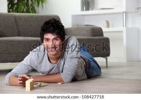 Man playing with dominoes at home - stock photo