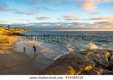 Man playing with his dog at  a beach at sunset - stock photo