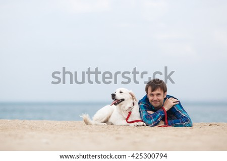 Man playing with his dog, golden retriever on a beach. young caucasian male on beach while walking with dog on sand - stock photo
