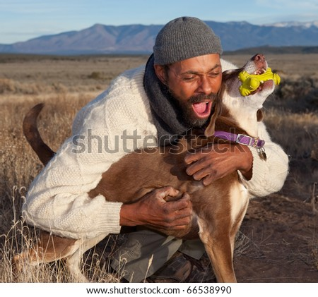 Man playing with his dog. Goofing, petting and howling. - stock photo