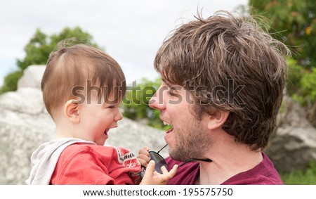 Man playing with his son on the beach - stock photo
