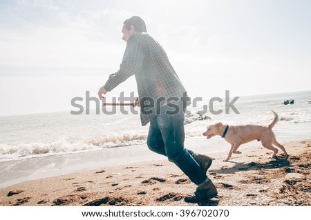 man playing with labrador dog on beach