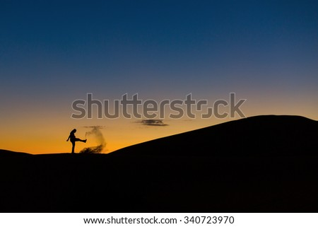 Man playing with sands in desert at sunset - stock photo