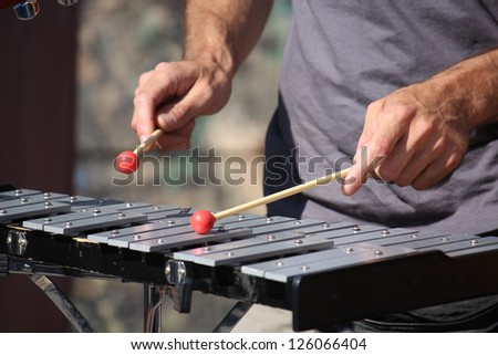 Man playing xylophone with nice red drumstick - stock photo
