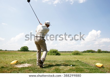 man plays golf