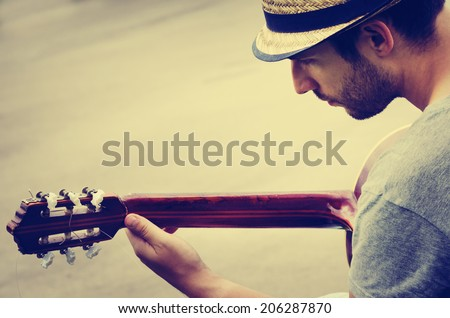 man plays the guitar on the street. retro style. - stock photo