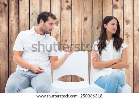 Man pleading with angry girlfriend against wooden planks - stock photo