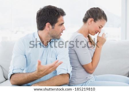 Man pleading with his crying partner on the couch at home in the living room - stock photo