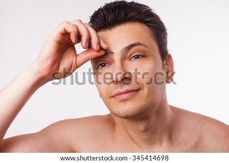 man plucking eyebrow - stock photo