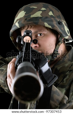 Man pointing a rifle in studio. Closeup