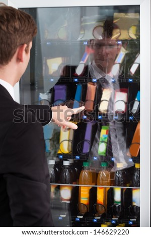 Man pointing at chocolate in display cake - stock photo