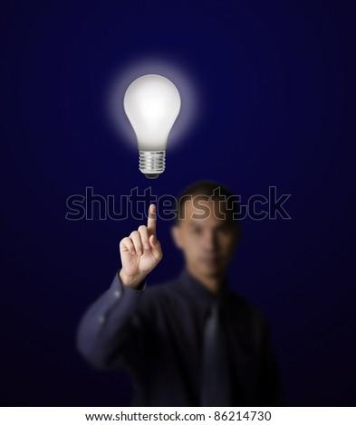 man pointing at shiny light bulb - stock photo