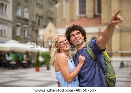 Man pointing at something while sightseeing with girlfriend.