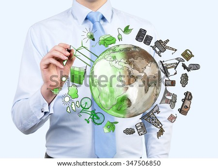 man pointing at the brown picture of oil industry components and green eco energy arranged in circle, earth in the centre, concept of environment - stock photo