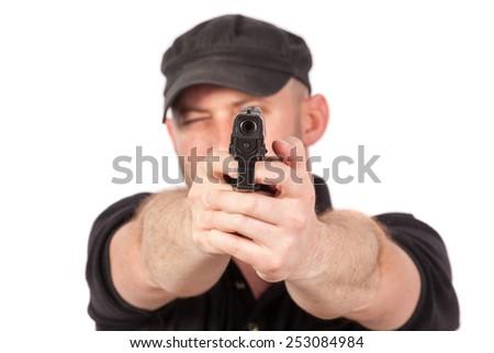Man pointing gun, isolated on white. Focus on the gun - stock photo
