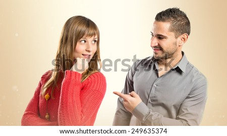 Man pointing his girlfriend over ocher background