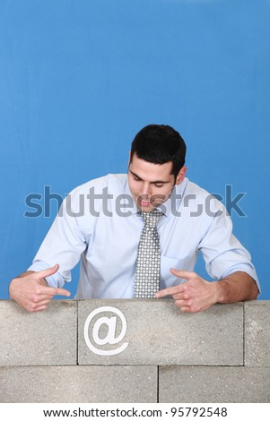 Man pointing towards at symbol stuck to wall - stock photo