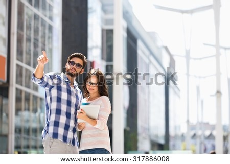Man pointing while woman using digital tablet outside building - stock photo