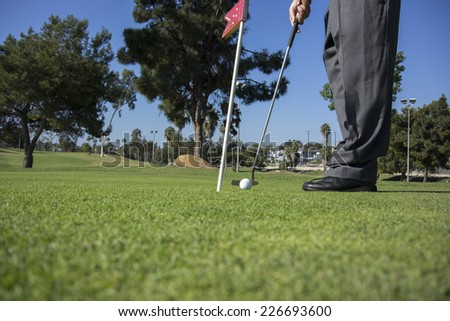 Man poised to make a putt/Putting and Golfer/Mid morning golfer attempting to make a putt - stock photo