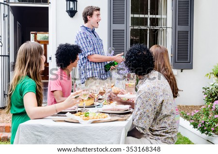 Man pops champagne with group of friends having a gathering party, sitting around a table with plenty of food
