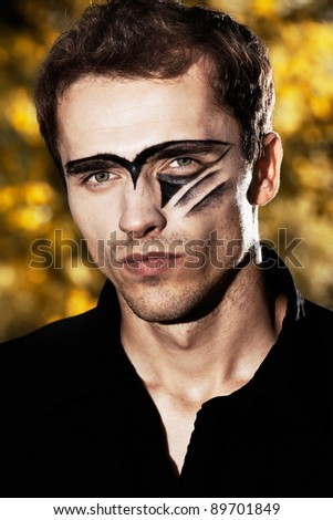 man portrait, hard handsome male model with military makeup - outdoor shot, natural background - stock photo