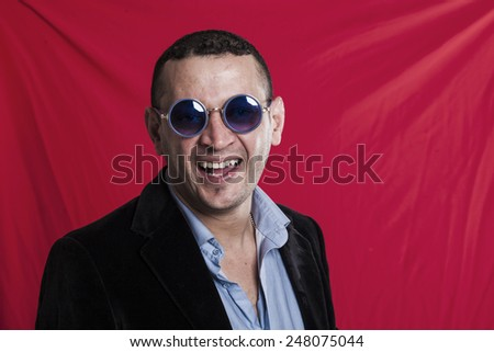 Man portrait wearing sunglasses and laughing - stock photo