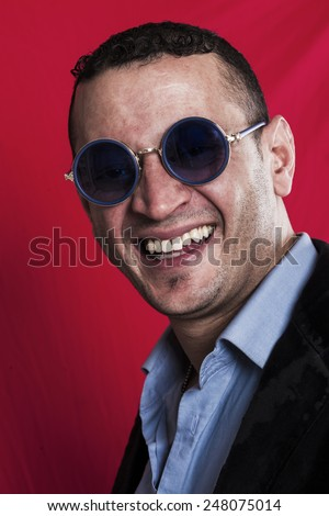 Man portrait wearing sunglasses and laughing closeup - stock photo