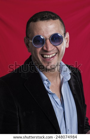 Man portrait wearing sunglasses and laughing vertical - stock photo