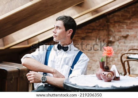 Man poses in cafe with rose on the table - stock photo