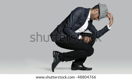 Man poses on one knee in studio