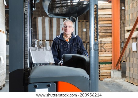 Man posing in a reach truck in a warehouse, in the background there are pallets with cardboard boxes piled up.  - stock photo