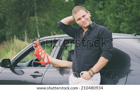 Man posing near the car with woman legs out the window.