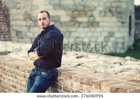 Man posing outside, leaning on a brick wall - stock photo