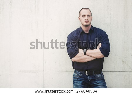 Man posing outside, leaning on concrete wall - stock photo
