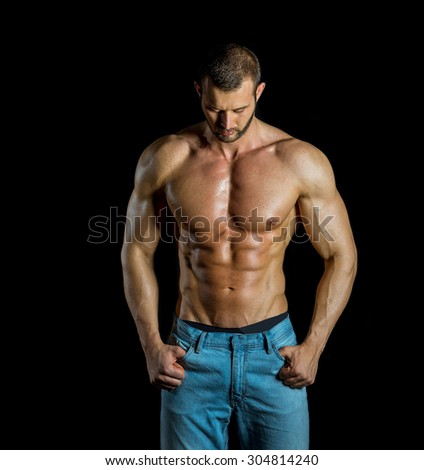 Man posing wearing jeans in front of black backgroud - stock photo
