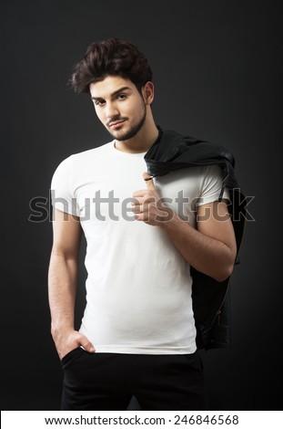 Man posing with black leather jacket, studio shot, dark background - stock photo