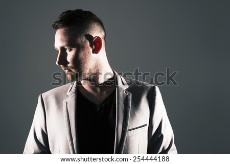 Man posing with dark background and hard lighting