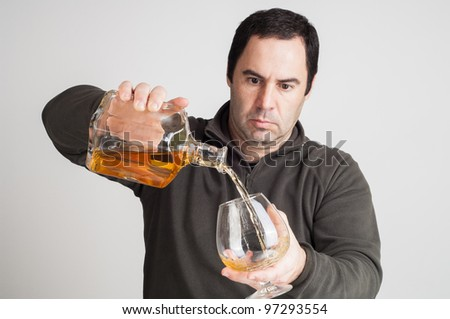 man pouring  a glass of whiskey on casual clothes