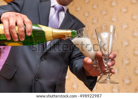 man pouring Champagne in two glasses closeup low angle shot