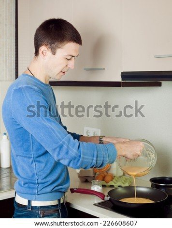 Man pouring dough  in frying pan at home kitchen