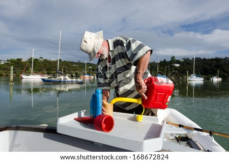Man pouring fuel into a cup tank of his boat from a red gas canister. - stock photo