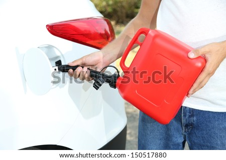 Man pouring fuel into gas tank of his car from red gas canister - stock photo